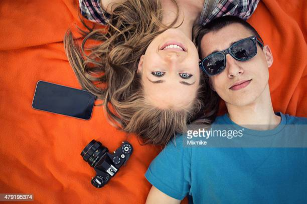 Teenage couple laying on a picnic blanket