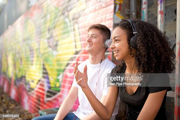 Teenage couple listening to mp3 player against wall with graffiti