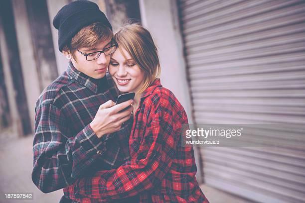 携帯電話を見ている 10 代のカップル