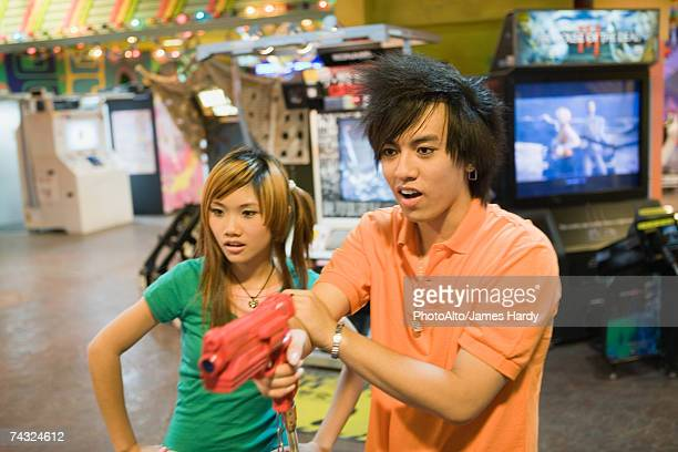 Teenage couple playing game in video arcade