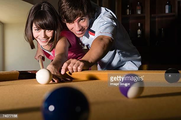 Teenage couple playing pool