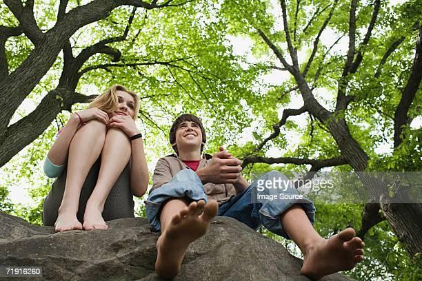 Teenage couple relaxing on a rock