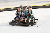 Teenage couple riding go carts at amusement park