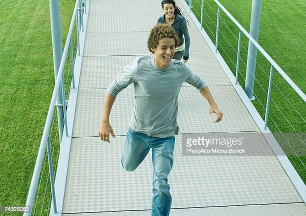 Teenage couple running on walkway