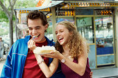 Teenage Couple Sharing a Waffle on a Disposable Plate