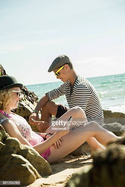 Teenage couple sitting at waterside of the beach wearing using smartphones