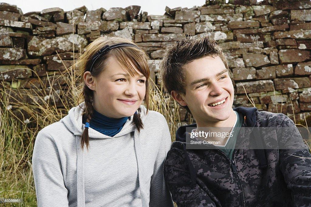 Teenage couple sitting near rock wall : Stock Photo