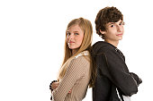 Teenage couple standing back to back with arms crossed