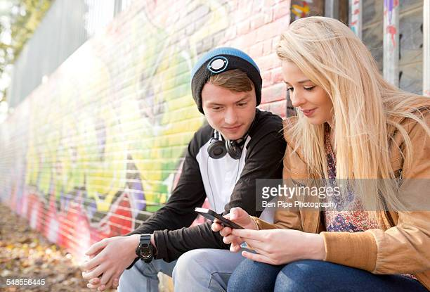 Teenage couple using smartphone against wall with graffiti
