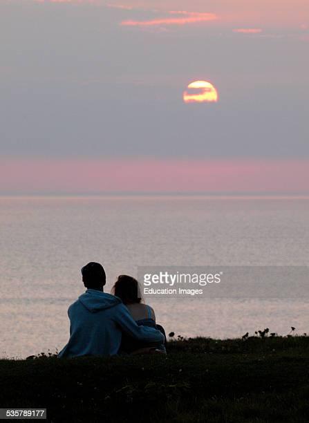 Teenage couple watching the sunset over the sea Bude Cornwall UK