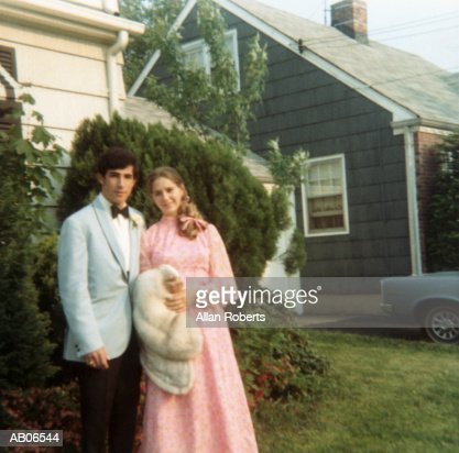 Teenage couple (16-18) wearing formal attire on lawn, portrait