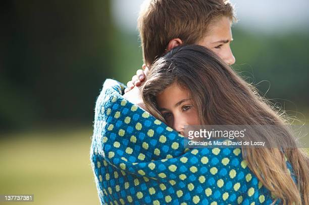 Teenage couple wrapped in blanket