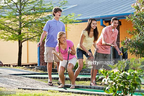 Teenage couples playing miniature golf