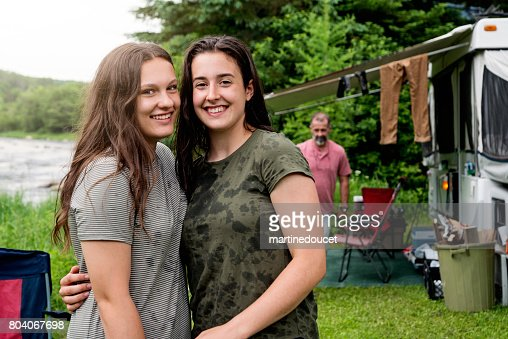 Teenage cousins hugging in camping outdoors in summer. : Stock Photo