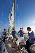Teenage crew raising the sail on a yacht.