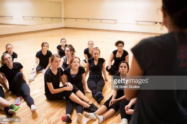 Teenage dancers listening to teacher in studio