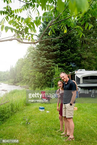 Teenage daughter showing affection to father in summer camping. : Stock Photo