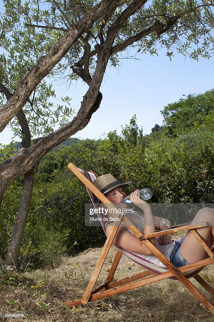 Teenage drinking water in deckchair : Stock Photo