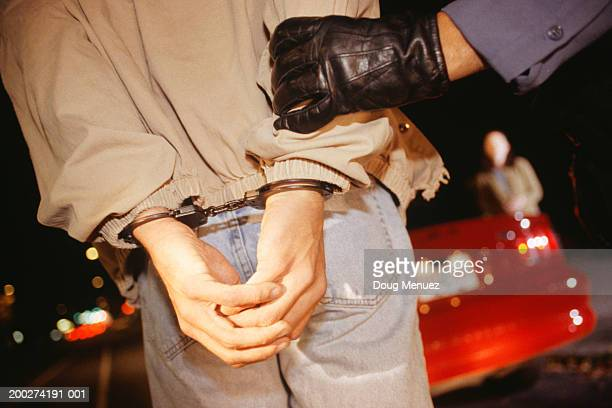 Teenage driver (16-17) being led away in handcuffs, mid section