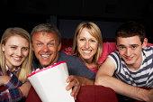 Teenage Family Watching Film In Cinema