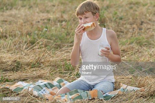 Teenage farmer boy eating fresh white bread : Stock Photo