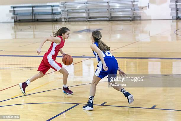 Teenage female basketball player one on one against another girl