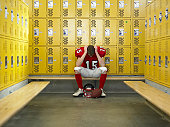 Teenage football player (15-17) hanging head in locker room