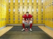 Teenage football player (15-17), sitting in locker room, portrait