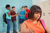 Teenage friends gossip, talk about an African descent classmate behind her back at school setting.  They use a various mobile devices to cyber-bully the girl who is showing depression emotion in foreg