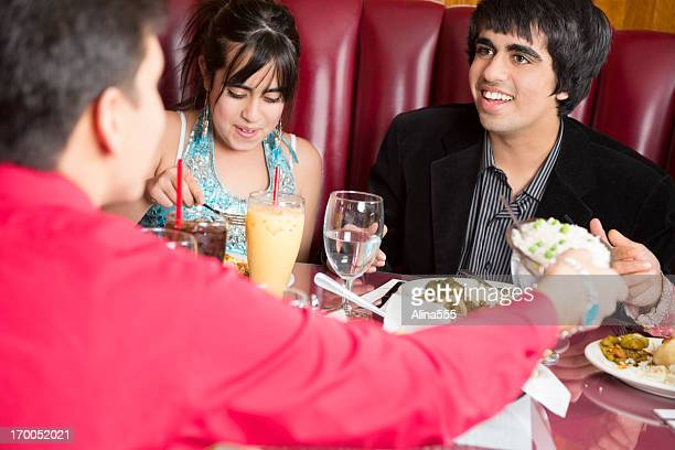 Teenage friends eating lunch at the indian restaurant