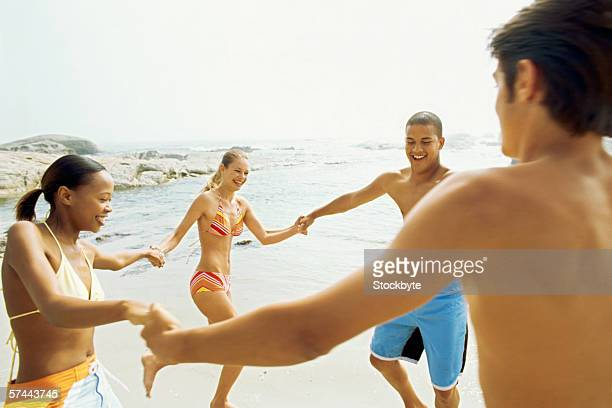 Teenage friends holding hands at the beach