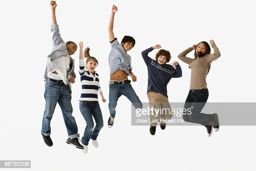 Teenage friends jumping in mid-air : Foto de stock