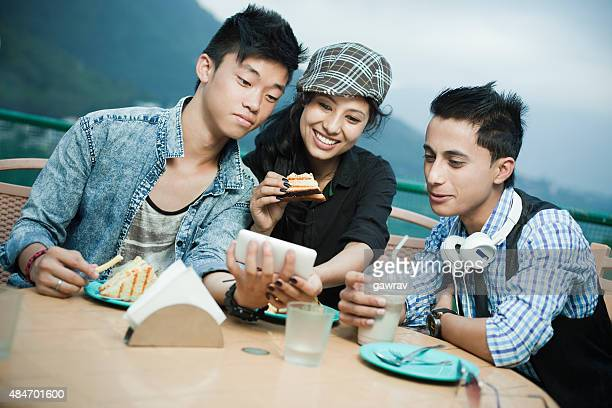 Teenage friends of different ethnicity with Smartphone enjoying at cafe.