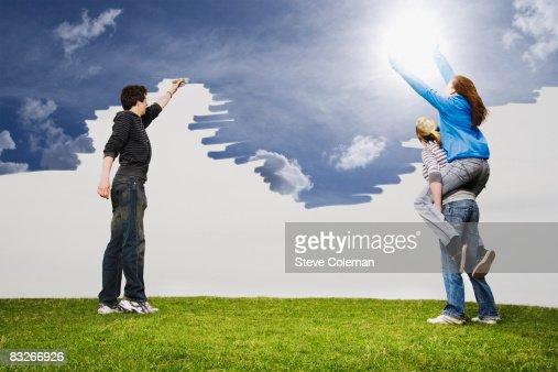 Teenage friends painting sky blue : Stock Photo