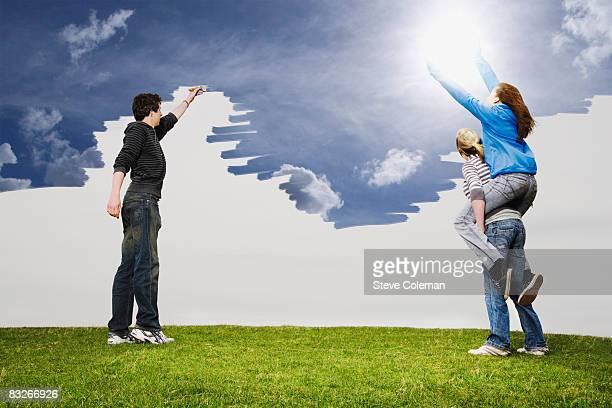 Teenage friends painting sky blue