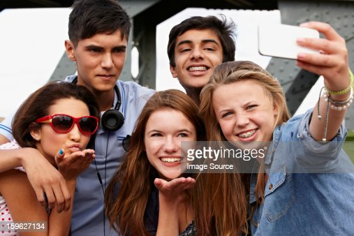 Teenage friends photographing themselves with smartphone : Stock Photo