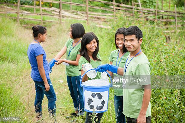 Teenage friends picking up trash to recycle. Park setting.
