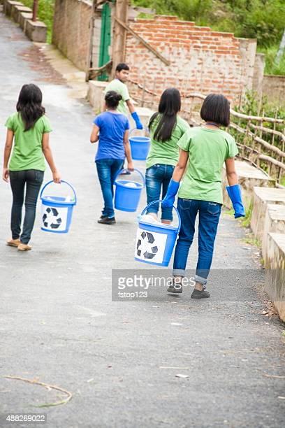 Adolescents de ramasser les déchets à recycler. Cadre en bord de route.