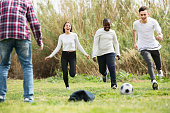 Group of smiling  teenage friends playing football outdoors in autumn day