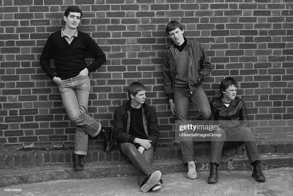 4 teenage friends pose up against a brick wall in 1980 UK 1980