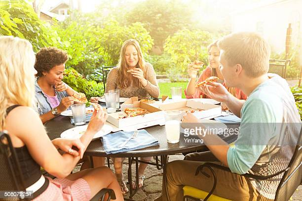 Teenage Friends Sharing Pizza Dinner at Summer Backyard Patio Table