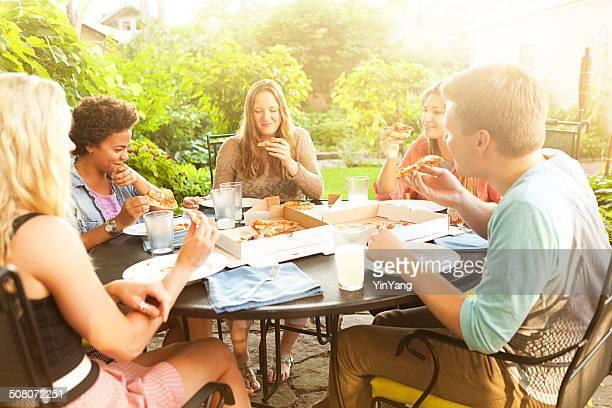Amici avendo una Pizza per cena in un Patio all'aperto sullo sfondo