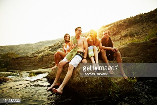 Teenage friends sitting on rock at sunset smiling : Stock Photo