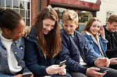 Teenage Friends Using Mobile Phones In Urban Setting