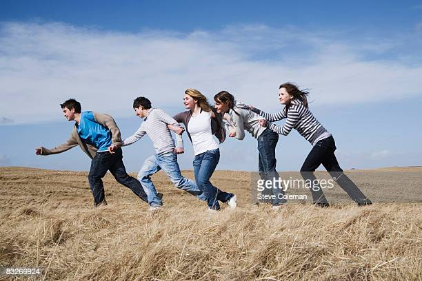 Teenage friends walking in a row in field