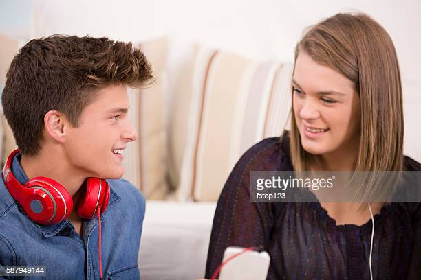 Teenage friends with headphones, smart phone at home.