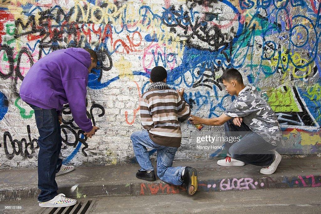 Teenage gang doing graffiti on a wall