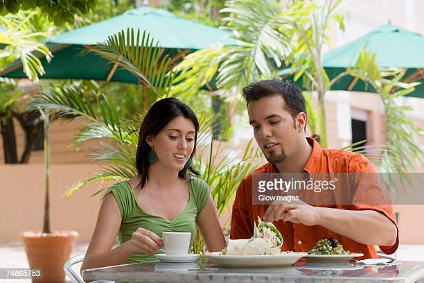 Teenage girl and a mid adult man sitting in a restaurant