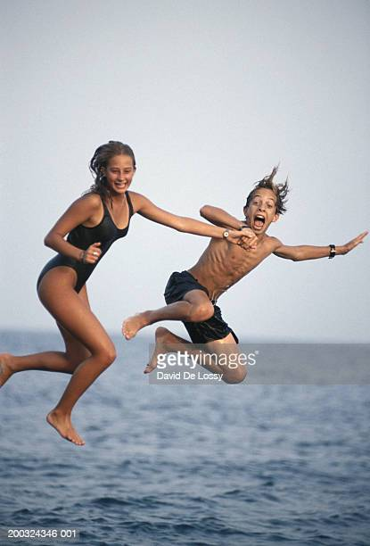 Teenage girl and boy (10-17) diving into sea