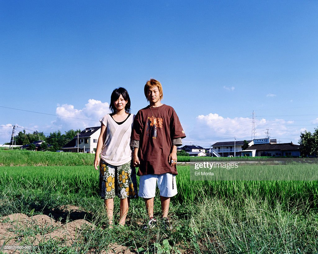 Teenage girl and boy (16-18) in open field, portrait : Stock Photo